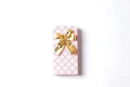 Pink gift box with a large gold bow. White background. Holiday concept, flat lay, top view Foto de archivo