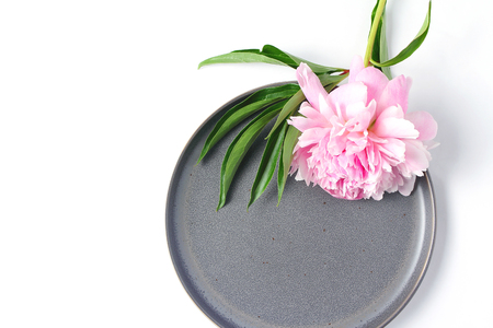 Minimalistic composition on a white background. fresh peony flower and gray dish on white background. top view, creative layout