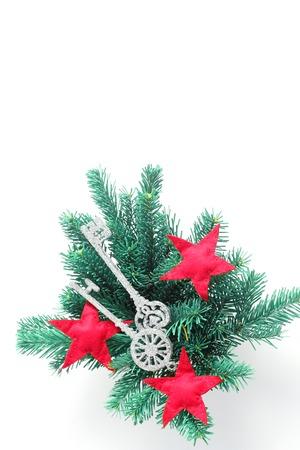 Weihnachtsarrangement von Fichtenzweigen und Spielzeug in Form von Schlüsseln und Sternen. Flache Lage, Draufsicht, vertikaler Rahmen Standard-Bild