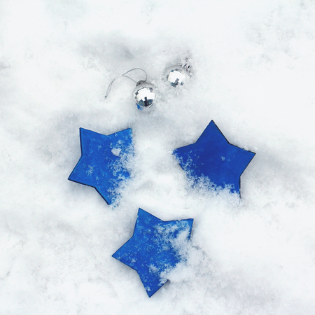 Christmas toys on snow. Three blue stars and silver balls. Top view, flat lay, square.