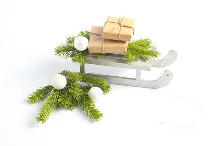gifts wrapped in craft paper eco. Christmas composition with silver sleighs. New Years minimal concept Stok Fotoğraf