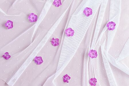 floral pattern. white fabric in form of veils and pink flowers. flat lay, top view