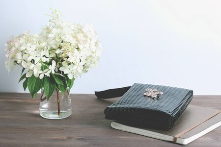 composition on a dark wooden background. bouquet of white hydrangeas and notebook.