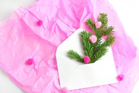 Christmas concept. composition on a pink background. white open envelope, spruce branches and multi-colored pompons shot from the top. flat lay, copy space. Standard-Bild - 129486592