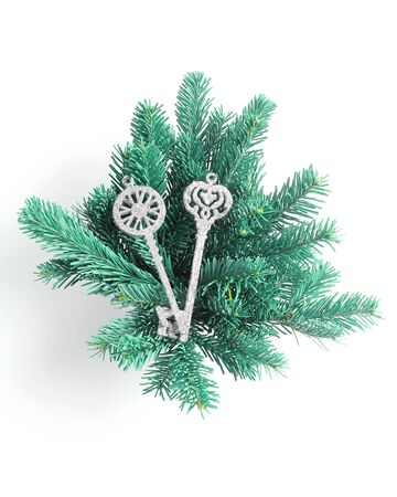 Christmas arrangement of branches of spruce and toys in the form of keys in silver. Flat lay, top view, vertical frame. 写真素材