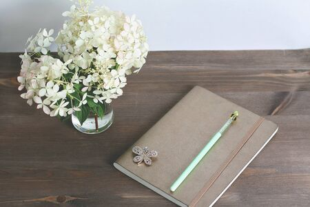 notepad with white hydrangea flowers in glasses vase on vintage wooden table. view from above. Stok Fotoğraf - 129486767