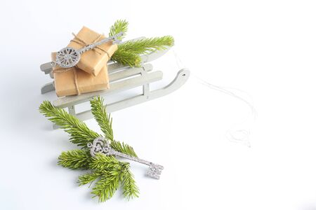 Christmas sleigh with gifts. New Years concept. decorative toys in the form of silver key and green branches of spruce.
