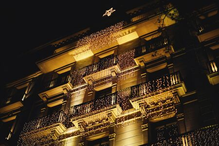 Decorated house with christmas lights. many garlands hung on the balconies of the historic building in Barcelona in the form of a Christmas tree with a star.