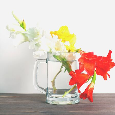 bouquet of gladioli in a glass vase on a wooden table. square frame. Banco de Imagens
