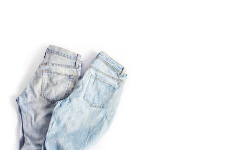 two folded pairs of jeans in light blue on a white background. space for text, flat lay, top view. Stock Photo