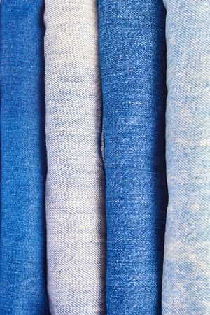 stack of denim trousers in close-up. textured background of blue color. vertical frame. Stock Photo