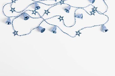 new year concept. Christmas garlands with stars and bells blue color on a white background. flat lay, top view, copy space.