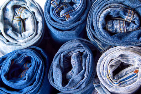 denim in various shades of blue, beautiful textured background of rolled jeans.