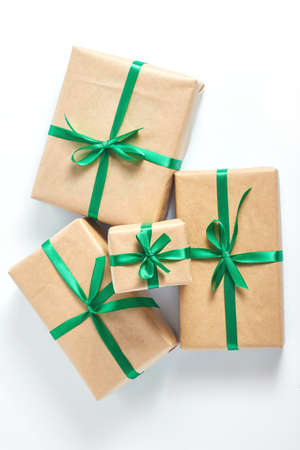 holiday concert. gifts wrapped in craft paper and tied with a green satin ribbon on a white background. space for text, flat lay.