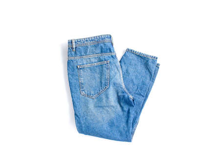 folded blue jeans on a white background. modern casual clothing. flat lay, copy space.