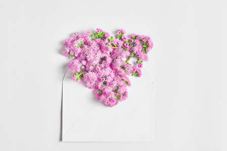 simple flat layout with flowers and an envelope on a white background. top view, copy space.