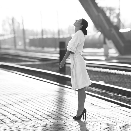 Black and white shoot of woman on train station; photo