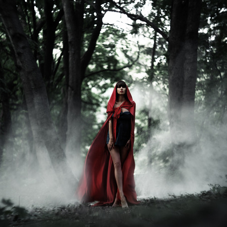 cloak: Beautiful dark-haired girl in a red cloak was lost in the wild forest. Little Red Riding Hood story. Fairy tale and legend. Grain added