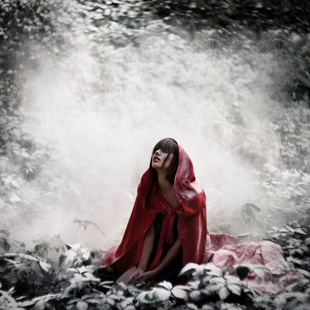 Beautiful dark-haired girl in a red cloak was lost in the wild forest. Little Red Riding Hood story. Fairy tale and legend. Grain added
