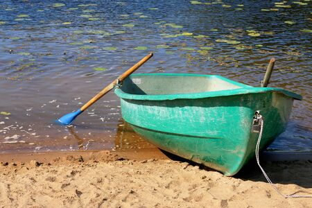 Fishing boat in a calm lake water. Old fishing boat in a still lake water. Summer. Beach. Lake.