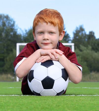 Cheerful little boy with ginger hair posing with a soccer ball. Portrait of a kid in sportswear. Little boy lying on the green lawn. Soccer champion