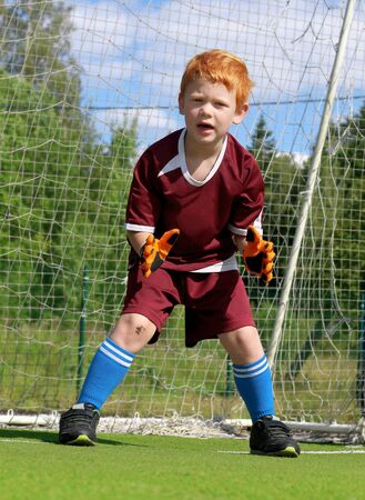 Goalkeeper kid is waiting to catch a ball from a penalty kick on a soccer stadium. Cheerful little boy with ginger hair. Footballer in sports clothes