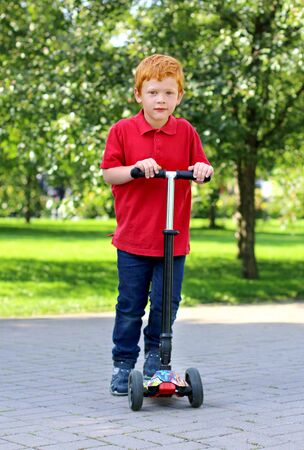 Child learn to ride scooter in a city park on sunny summer day. Cheerful little boy with ginger hair posing with a scooter. Active leisure and outdoor sport for child 스톡 콘텐츠