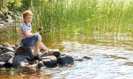 Little boy with ginger hair is fishing on the lake. Sunny summer day. Texture of water surface. Stones. Pier beach