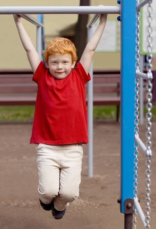 Boy on monkey bars. Little boy hanging on gym activity center of school playground. Outdoor activity for kids. Sport. Fashion kid. Cute boy in summer clothes