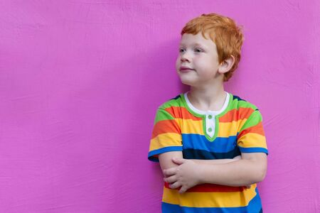 Fashionable little boy. Red-haired handsome kid model wearing trendy striped casual shirt posing against pink wall background enjoying good summer weather 免版税图像