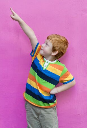Fashionable little boy in striped t-shirt looking and pointing finger. Red-haired handsome kid model posing against pink wall background enjoying good summer weather