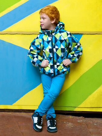 Fashionable little boy. Red-haired handsome kid. Model wearing trendy jacket posing against striped wall background enjoying good autumn-spring weather. Playing on outdoor playground