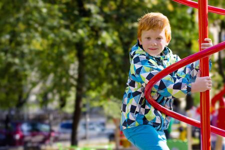 Child playing on outdoor playground. Fashion kids play on school or kindergarten yard. Pretty boy. Cute boy in spring-autumn clothes. Red-haired handsome model posing