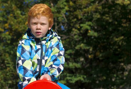 Child playing on outdoor playground. Boy play on school or kindergarten yard. Kid with curly ginger hair. Portrait. The red-haired boy stares intently at the camera 免版税图像