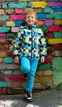 Fashionable little boy. Red-haired handsome kid. Model wearing trendy jacket posing against colorful brick wall background enjoying good autumn-spring weather. Playing on outdoor playground