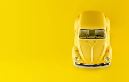 Yellow car on yellow background. Valentine's day. International Happy Women's Day. Flower delivery. 8 March. Summer. Taxi travel concept. Toy car. Banner. 免版税图像