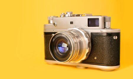 Retro, vintage film photo camera isolated on yellow colourful trendy modern fashion background. Camera lens with reflections. Film camera. Creative, minimalism 免版税图像