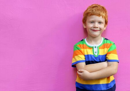 Fashionable little boy. Red-haired handsome kid model wearing trendy striped casual shirt posing against pink wall background enjoying good summer weather 스톡 콘텐츠