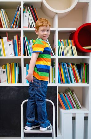 Adorable red-haired little boy, standing on stairs in library. Childs Brain Development, learn to read, Cognitive Skills. Getting ready for school. Multi colored bookshelf in the library. Chalkboard