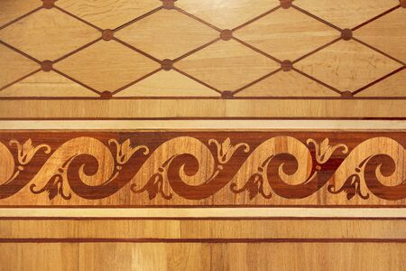 Old wooden parquet with an interesting plant pattern. Decorative wooden tile. Top view grunge wood. Wooden parquet background texture. Warm, yellow, red 免版税图像
