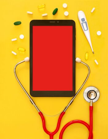 Red stethoscope and a tablet PC with a medical app, copyspace Isolated yellow background. Concept telemedicine, mock up, top view, pills, medication, doctor online, thermometer