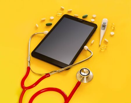 Red stethoscope and a tablet PC with a medical app, copyspace Isolated yellow background. Concept telemedicine, mock up, top view, pills, medication, thermometer, doctor online, phonendoscope