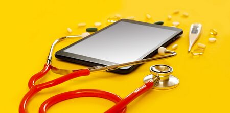 Red stethoscope and a tablet PC with a medical app, copyspace Isolated yellow background. Concept telemedicine, mock up, top view, pills, medication, thermometer, doctor online