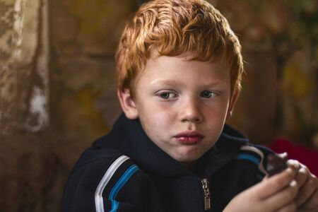 Portrait homeless unclean kid. Hungry child with big clear eyes eating. Red-haired little boy. Close-Up. Concept of social problems. Life on the street