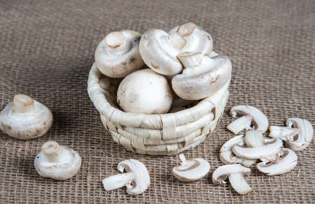 Closeup of group raw whole and sliced champignon mushrooms in wicker basket on natural sackcloth background