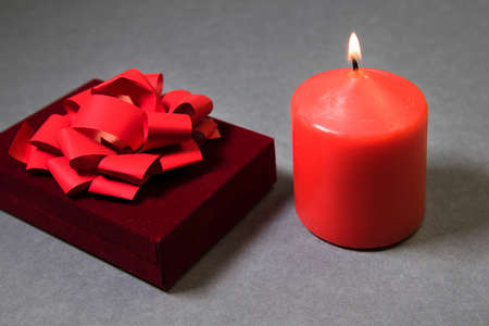 Red gift box with ribbon and candle burning on gray background. Merry christmas and new year wrapping