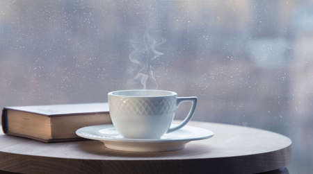 White coffee cup with smoke and brown book on table in cafe. Late autumn and comfort concept. Window view. Snowing outside. Selective focus.