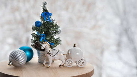 Christmas banner with new year tree, dcorations and white toy horse on table near window in cafe, winter snow background outside. Copyspace