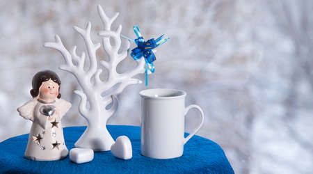 Christmas banner with coffee mug, white tree and toy angel on table near window in cafe, winter snow background outside. Copyspace