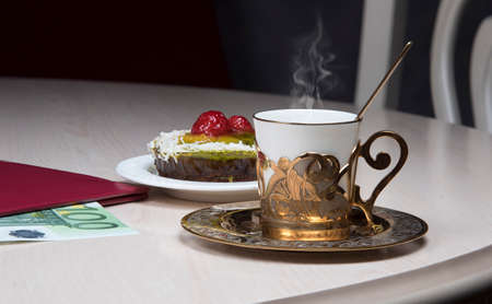 Golden coffee cup, fruits cake and cash 100 euro on table in cafe, luxurious elegance style concept.